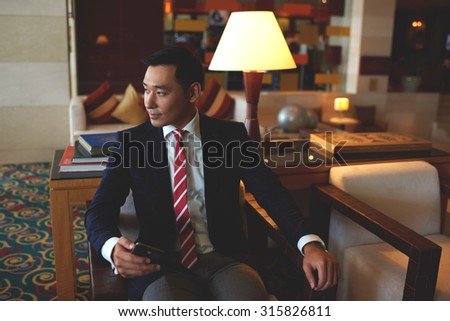 Young successful asian businessman dressed in formal wear holding mobile phone while sitting in modern office,confident rich men entrepreneur waiting for a call on his cell telephone during work break - stock photo
