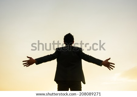 Young successful business man standing with arms and sunset background - stock photo