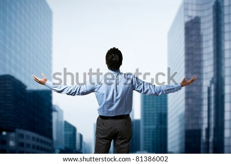 Young successful business man standing with arms wide open in front of buildings business center - stock photo