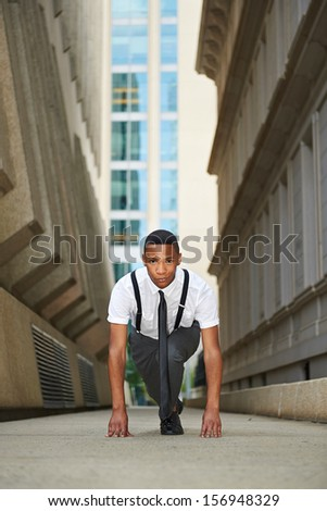 Young successful business man starting a race - stock photo
