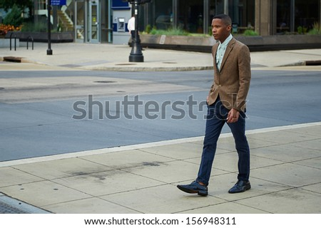 Young successful business man walking in the city - stock photo