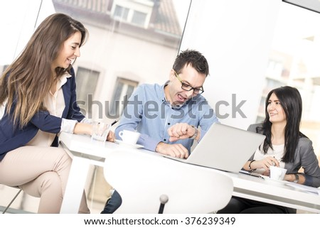 Young successful business people interacting, discussing and sharing ideas in bright modern office. Focus on man in the middle. Deadline concept - stock photo