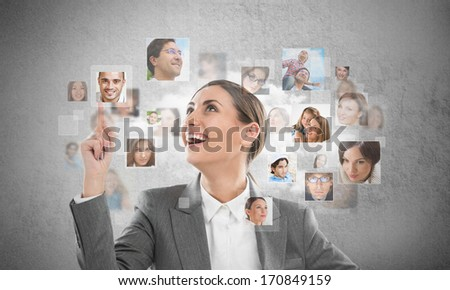 Young successful business woman looking at people portraits. International communication and recruitment concept - stock photo