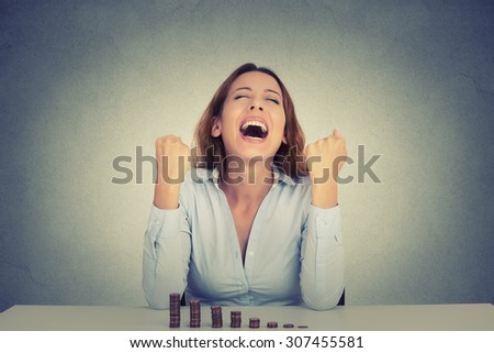 Young successful business woman sitting at table with growing stack of coins celebrates screaming fists pumped. Financial freedom target success concept   - stock photo