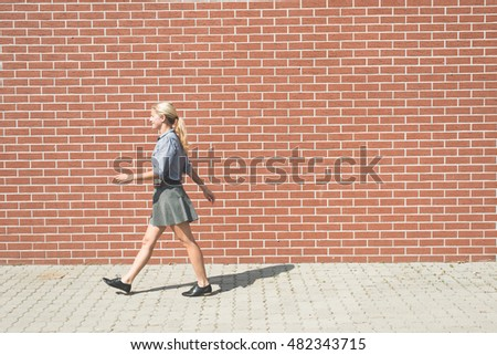 Young successful business woman walking against brick wall