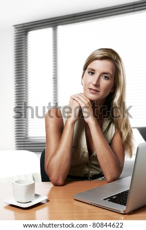 young successful business woman working at home / office with a laptop and coffee - stock photo