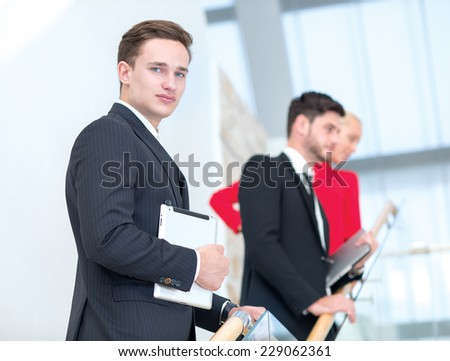 Young successful businessman confidently looks at the camera while standing with tablet. Two his colleagues are standing on the background