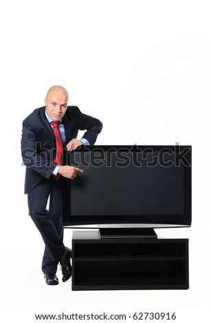 Young successful businessman in a black suit with a large plasma television on the bedside table. Isolated on white background - stock photo