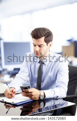 Young successful businessman making phone call or writing/reading an SMS. Text messaging - stock photo