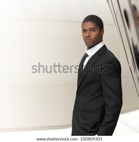 Young successful businessman posing in elegant suit against modern background with copy space - stock photo