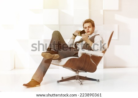 young successful businessman sitting in expensive armchair and talking on mobile phone. Fashion style toned portrait in modern office interior - stock photo
