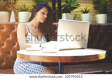 Young successful businesswoman focused and thoughtful work on her laptop computer during coffee break in a expensive restaurant, female freelancer working via net-book on-line on the distance, filter - stock photo