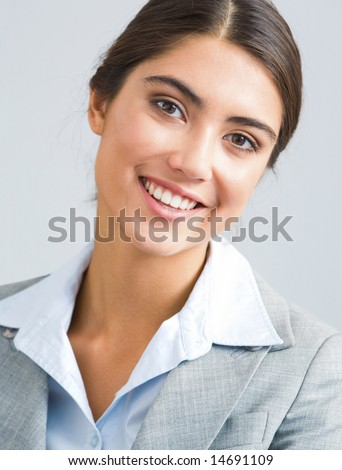Young successful businesswoman looking at camera with smile - stock photo