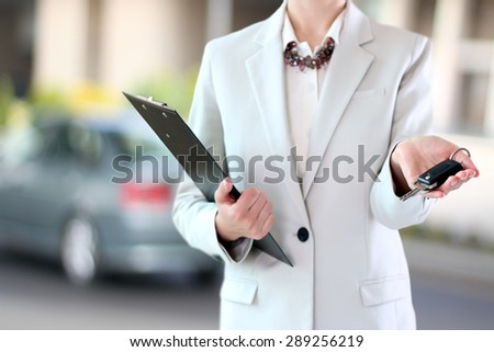 Young successful businesswoman offering a car key.  - stock photo