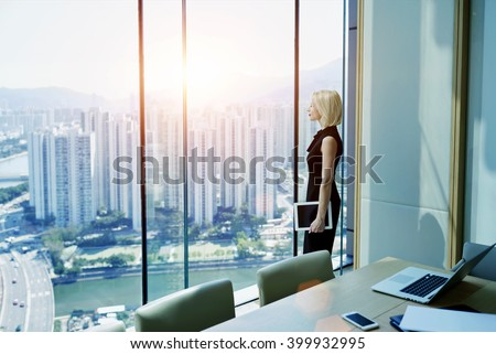 Young successful businesswoman with digital tablet in hand is thinking about future of her construction company, while is standing in modern office interior near window with Cityscape view. Copy space - stock photo