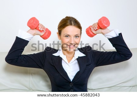 Young successful businesswoman with dumbbells - stock photo