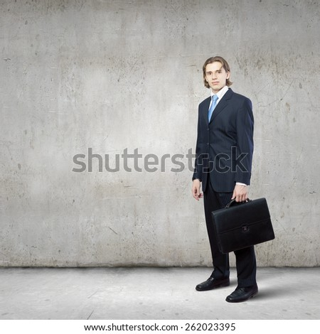 Young successful handsome businessman in suit in empty room - stock photo