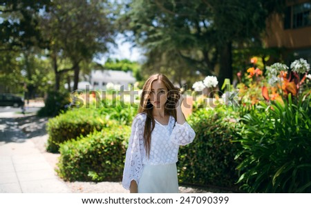Young successful lady walking down the  blossoming street - stock photo