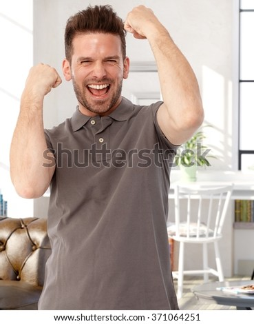 Young successful man shouting happy with raised arms and clenched fists.