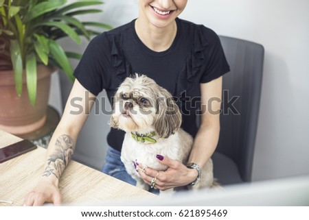 Young successful modern tattoo business woman working in pet friendly office