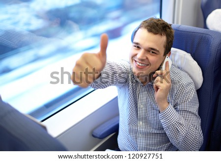 Young successful smiling businessman in modern high speed train is talking smartphone and showing his thumb up - stock photo