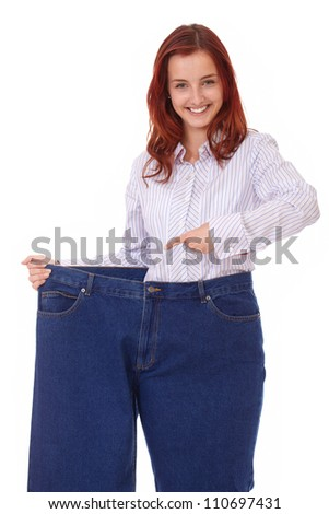 Young successful smiling happy beautiful slim girl in blue jeans, isolated on white - stock photo