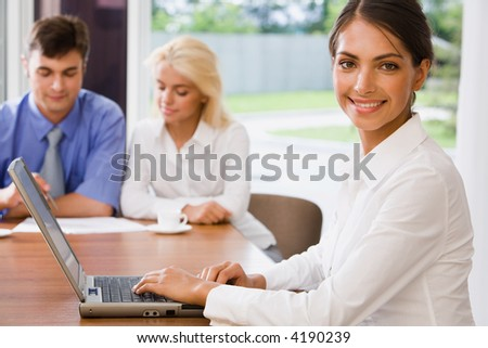 Young successful smiling woman in a working environment on a background of her colleagues
