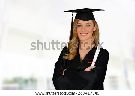 Young successful woman graduating from college holding a diploma - stock photo