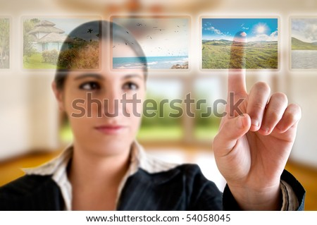 Young successful woman planning her vacations choosing options from digital touching screen - stock photo