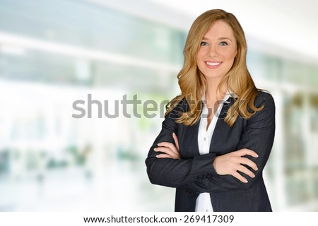 Young successful woman with crossed hands looking at camera - stock photo