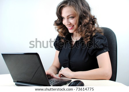 Young successful woman working at desk with laptop - stock photo