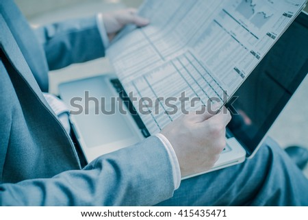 Young successful young man holding a newspaper - stock photo
