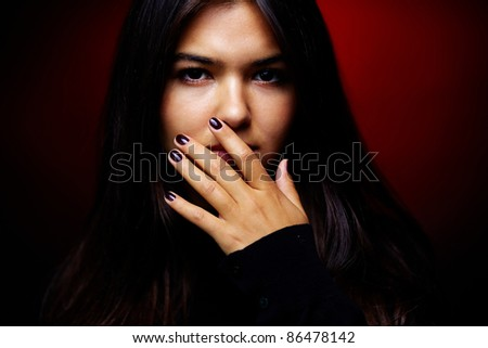 Young sullen woman looking at camera in the dark - stock photo