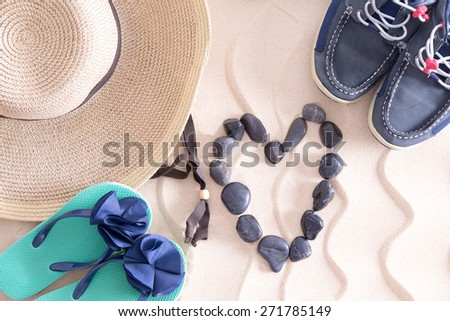Young summer love at the beach in a conceptual image with a straw sunhat, slip slops and boys shoes surrounding a pebble heart on golden beach sand with a decorative wavy pattern - stock photo