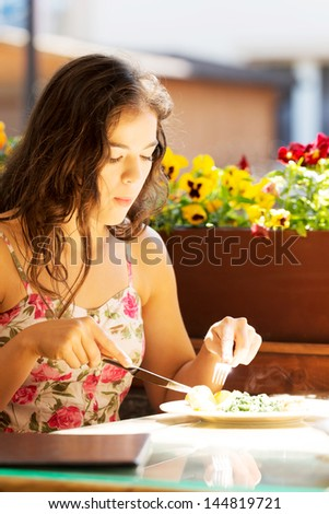 Young summer woman eating dinner in restaurant. - stock photo
