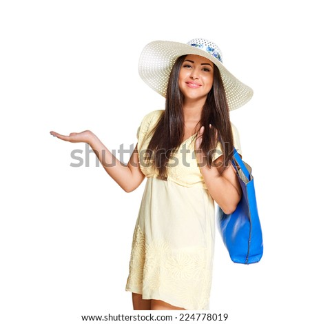 young sun-tanned woman  dressed in a lite summer yellow dress and a straw hat holding blue  bag, showing open palm,  smiling and looking in the camera, isolated on white background