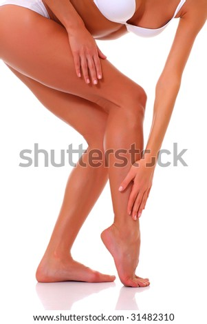 Young suntanned harmonous woman masses to itself feet, isolated on a white background, please see some of my other parts of a body images