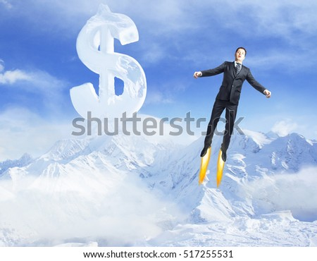 Young superman flying in bright blue sky with creative dollar sign above snowy mountains. Success concept