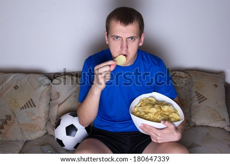 young supporter in uniform watching football on tv at home and eating chips - stock photo