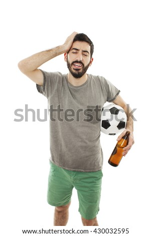 Young supporter man with ball and beer bottle watching football game, look disappointed. - stock photo