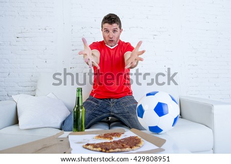 young supporter man with ball and beer bottle watching football game on television sitting at home couch in stress dejected and disappointed for failure shouting and complaining - stock photo