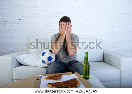young supporter man with ball pizza and beer bottle watching football game on television sitting at home couch covering his eyes sad dejected and disappointed for failure or defeat  - stock photo