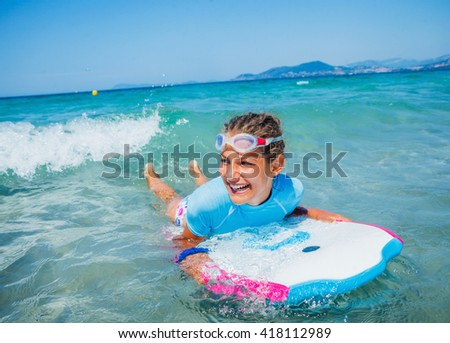 Young surfer girl is learning to ride a wave.