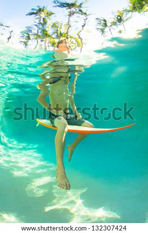 Young surfer paddling through the ocean
