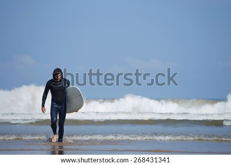 Young surfer sport man carrying his surfing board and going out the sea while on vacation during a sunny day, with an intense blue sky and big waves break on background