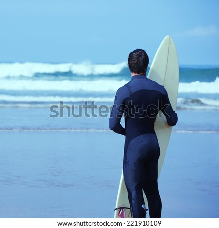 Young surfer standing on the beach enjoying amazing view of ocean, surfer man in wetsuit holding a surfboard and waiting the waves, professional surfer looking to the ocean away, filtered image - stock photo