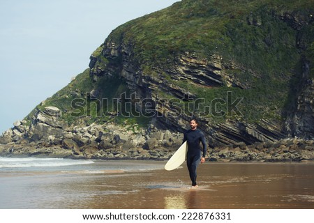Young surfer walking to the waves along beautiful shore, professional surfer in wetsuit carrying a surfboard runs along the sea with beautiful reflection in wet sand,beautiful ocean beach with rocks - stock photo
