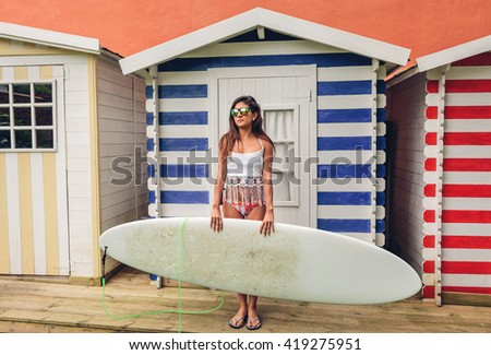 Young surfer woman with top and bikini holding surfboard - stock photo