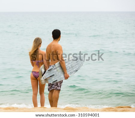 Young surfers couple with surfboards on the sandy beach