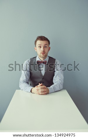 Young surprised business man in bowtie and jacket sitting at the table
